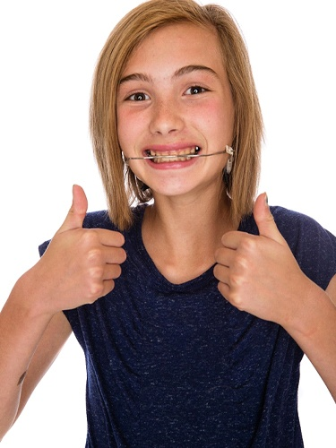 girl smiling headgear thumbs up