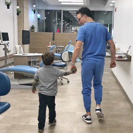 Dr. Justin holding hands with young child