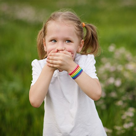 Little girl outside holding mouth
