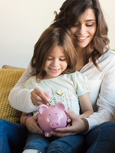 Mother and daughter putting change in piggy bank