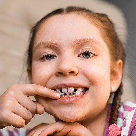 Young girl pointing to her braces