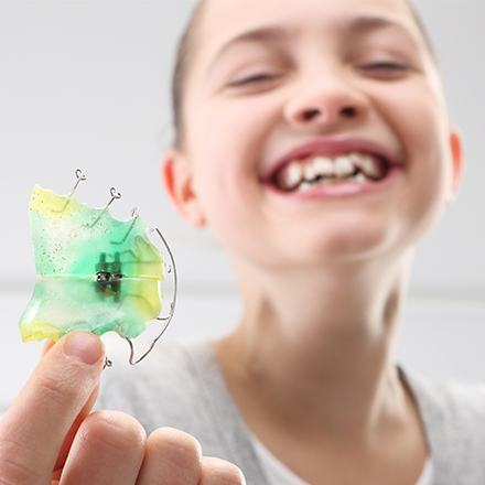 Laughing young girl holding her retainer