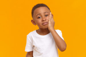 little boy with dental pain needing to see a pediatric dentist
