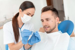 orthodontist holding Invisalign with patient